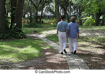 Lovers On Garden Path - A couple walking together on garden...