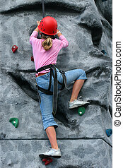 To The Summit - A young girl wearing a saftey harness and...