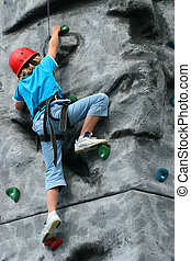 Steep Climb - A young girl wearing a safety harness and red...