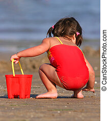 Gathering The Shells - Little girl in a red swimsuit and a...