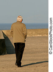 Old and Alone - Elderly man in drab clothing walking along a...
