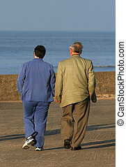 Hand In Hand - Elderly couple walking hand in hand on a...
