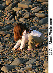 A Child Playing With Pebbles - A red headed child playing...