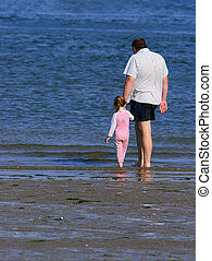 Togetherness - A father holding the hand of his daughter at...