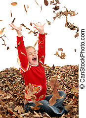 Girl Child Leaves - Happy 7 year old girl playing in a big...