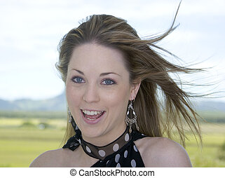 Beauty in the Breeze - Smiling young woman - hair blowing in...