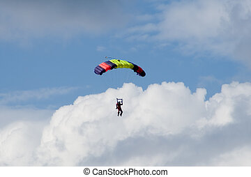 Skydiver in clouds with blue sky