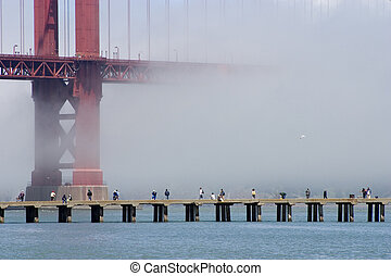 Fog Fishing - Fisherman on a cement pier with a fog shrouded...