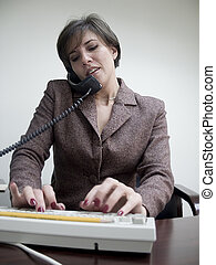 Multitasking - A woman sits at her desk on the telephone and...