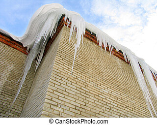 Big icicles on the roof of brick building