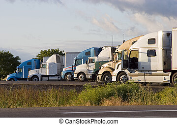 Line of Trucks 2 - Tractor-trailer trucks in a line at a...