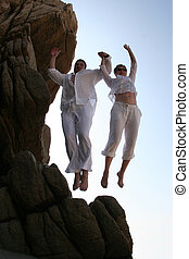 Cliff jumping - Couple jumping together from the top of the...