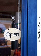 Open for business - Shop sign against a blue door