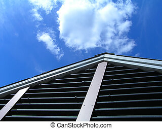 Gable of house against blue sky with clouds