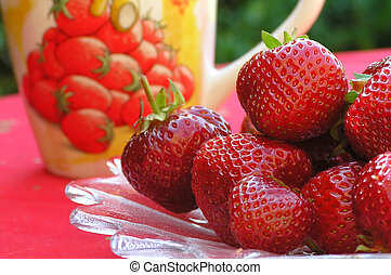 Strawberries on plate and with a strawberry mug