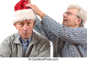 Putting on hat - Elderly woman putting a christmas hat on...
