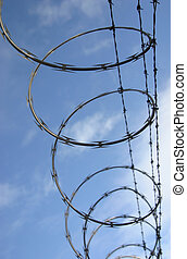 Razor Wire 1 - Razor wire spirals against the sky with...
