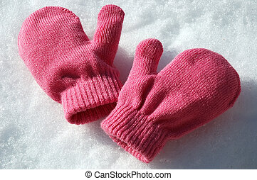Pink Mittens - Pink knit mittens laying on the snow.