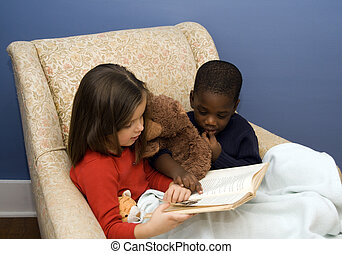 Story Time - Two small children reading a story in a big,...