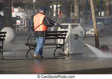 Sidewalk Cleanup - A city worker steam-cleans the sidewalk