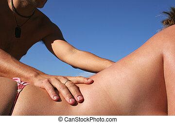 Beach Massage - Man giving topless woamn in bikini a a...