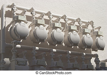 Water Meters - A line of water meters outside of an...