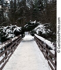 Snow Covered Bridge - A brown wooden snow covered bridge