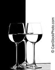 three wine glasses in backlight on the black and white...
