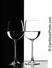 two wine glasses in backlight on the black and white...