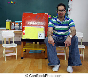 The teacher - Male teacher sitting in the classroom