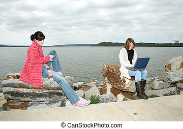 College Girls Outside with Laptop - Two beautiful young...