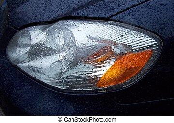 Automobile headlight in the rain.