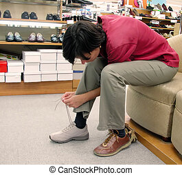 Trying new shoes - Girl trying new shoes in a shoes shop