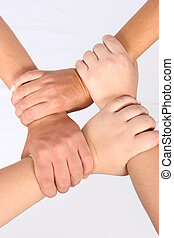 Interlocked hands of four people
