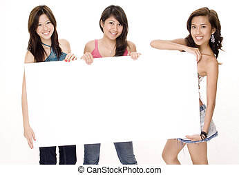 Blank Sign 1 - Three attractive young women hold a large...