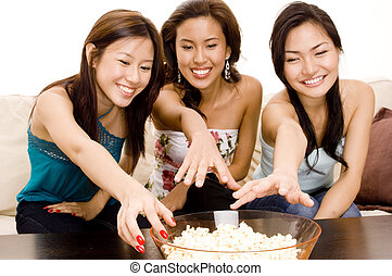 Reaching For Popcorn - Three attractive asian women reach...