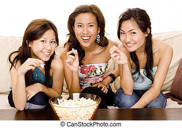 Got Popcorn - Three attractive young asian women sitting on...