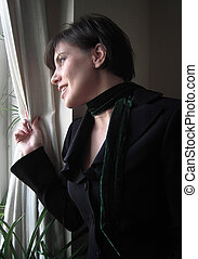 Outlook - A woman with short dark hair looks out of a window...