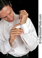 Man Wearing Cufflinks on black - A handsome man putting on...