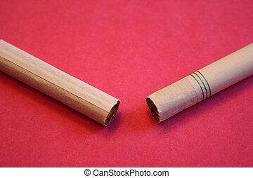 Broken Cigarette on Red - A broken cigarette on a red...