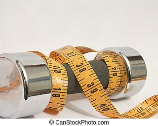 Fitness Tools - Hand weight and measuring tape on white...