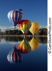 Three in a row - three hot air balloons floating over clear...