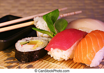 Sushi and Maki - Sushi, Maki and chopsticks on a glass plate...