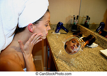 Woman in Mirror - Woman applies makeup in mirror at spa rest...