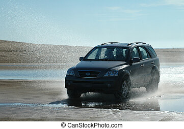 Fun on the beachII - A four-wheel-drive ploughs through the...