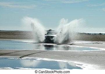 Fun on the beach - A four-wheel-drive ploughs through the...