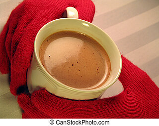 warming up - gloved hands holding a mug of steaming hot...