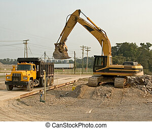 DumpTruck & Trackhoe - Large track hoe being used to fill...