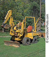 trenchrer - Plumbers using trencher to dig a ditch for a new...
