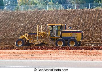 Grader - Road grader leveling hill for new highway, on...